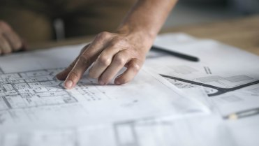 Hands of architects drawing notes and comments on construction plans